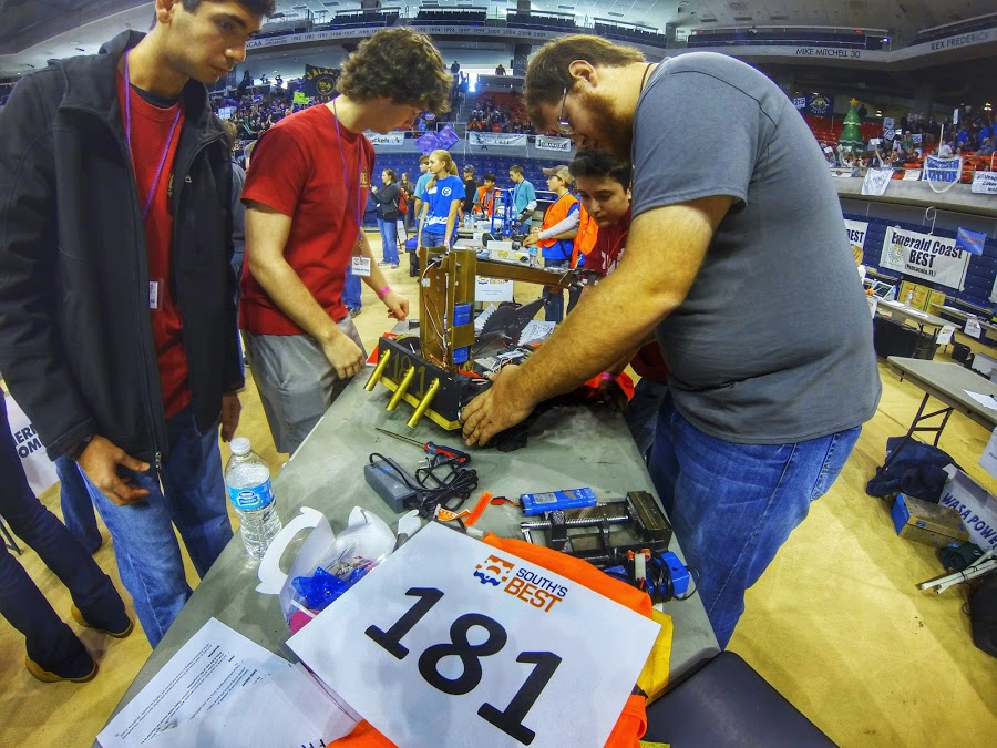 A group of teammates making changes to their robot at the South's BEST Robotics Championships.